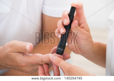Close-up Of Doctor's Hand Using Glucometer On Patient's Finger