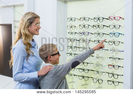 Mother and son selecting spectacles from display in optical store