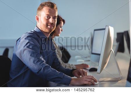 Portrait of mature student using computer in the computer room at college