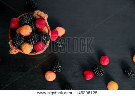 Mixed Of Red, Black, Yellow Raspberries In A Basket On  Wooden Background. Close Up. Top View. Copy