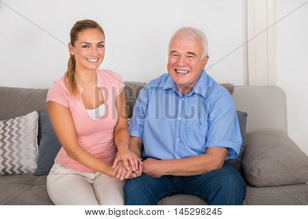 Smiling Young Woman Sitting On Sofa Holding Her Father's Hand At Home