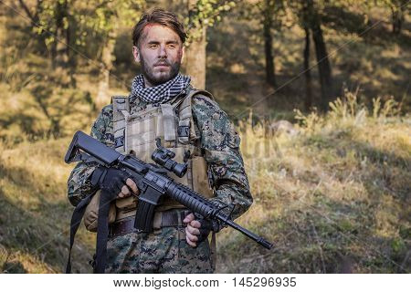 Soldier is waiting for battle in the forest with gun