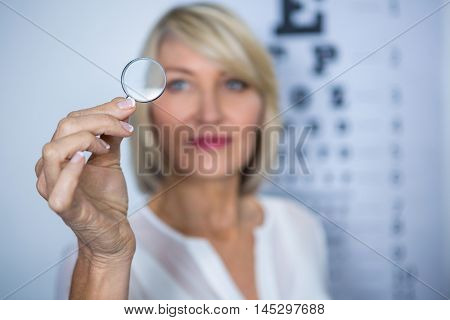 Female patient looking through magnifying glass in clinic