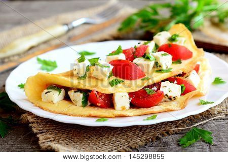 Home stuffed omelet on a plate. Egg omelet stuffed with tomatoes, cheese and green parsley. Vegetarian diet breakfast recipe. Fork, knife, cutting board on wooden background. Closeup