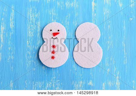 How to sew a Christmas snowman ornament. Step. Cut from white felt details for sewing Christmas tree ornament. On one side embroidered with black thread eyes and mouth, red thread snowflakes and nose