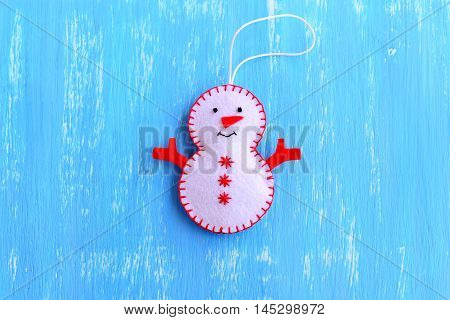 Fun felt Christmas snowman ornament isolated on a blue wooden background. How to make a Christmas snowman ornament. Step. Christmas tree decor idea for chilfren. Easy felt sewing crafts. Top view