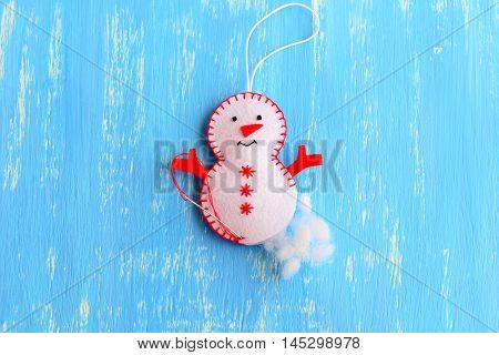 How to make a Christmas felt snowman ornament. Step. Stuff the felt Christmas snowman ornament with hollowfiber. Christmas tree sewing crafts for kids. Blue wooden background. Top view
