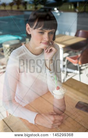 Thoughtful woman sitting in cafeteria with milkshake on table