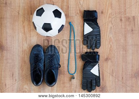 sport, football and sports equipment concept - close up of soccer ball, boots, whistle and gloves on wooden background