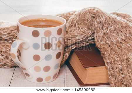 Cup of hot tea with lemon dressed in knitted warm winter scarf on brown wooden tabletop soft selective focus retro filter