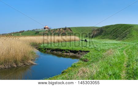 Rural landscape with small Ukrainian river Sura at early spring season.