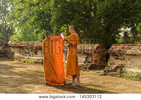 Asian novice helps to clothing another robe