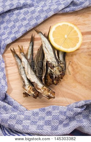 smoked sprats with slice lemon on a wooden board