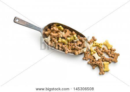 Dog food shaped like bones in scoop isolated on white background.