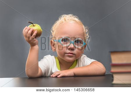 Child with glasses holding an apple sitting at the table on a gray background