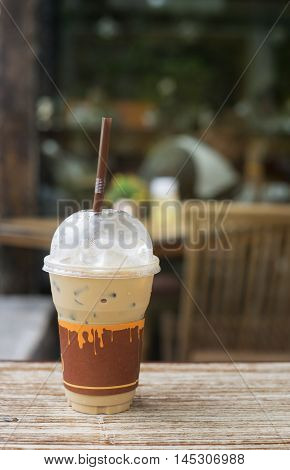 Iced Coffee In Takeaway Cup On Wood Table With Blurred Coffee Cafe Background,selective Focus