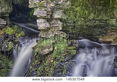 The small falls in Pavlovsk flowing between mossy stones and ruins