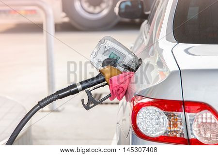 Hand hold fuel nozzle to add fuel in car at filling station.