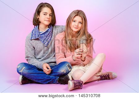 Happy teenage boy and girl sitting together over pink background. Friendship. First love.
