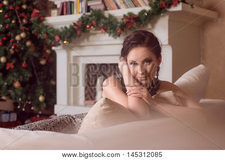 Dreamy girl lying on the sofa against the background of the Christmas tree