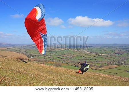 Paraglider launching his wing on Dartmoor in Devon