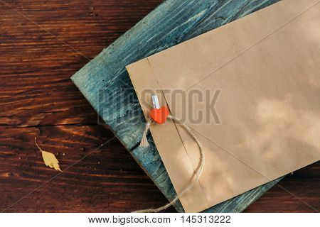 Red heart clothespin with blank brown paper envelope on grey wooden board and yellow leaf on timber background
