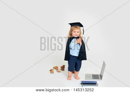 Little boy kid with smiling face in blue shirt and shorts black academic gown and cap standing near wooden blocks notebook and diaries isolated on white background