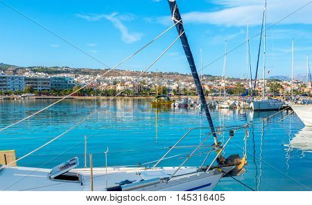 The view through the sails and ropes of the yacht on the coastline of the modern tourist districts of Rethymno Crete Greece.