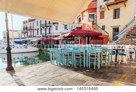 RETHYMNO GREECE - OCTOBER 16 2013: The wooden chairs and tables of the outdoor cafes and taverns in the old harbor on October 16 in Rethymno.