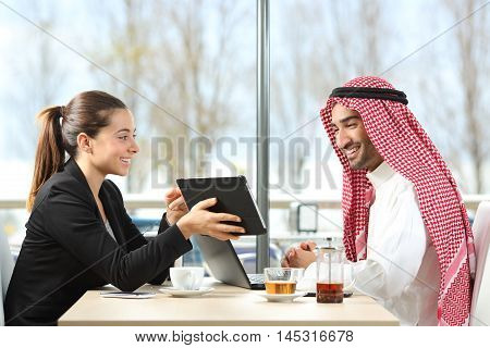 Businesswoman or saleswoman working with an arab man showing products in a tablet in a coffee shop