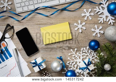 Top view of business desk with smart phone, post it, snowflakes and christmas decorations. High angle view with empty yellow sticky note for your text. Blue business xmas with snow fir tree.