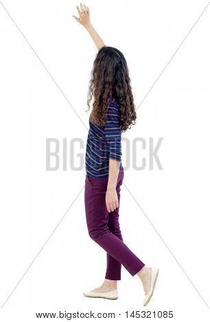 back view of walking woman welcomes. Long-haired curly girl goes past the camera welcoming someone.