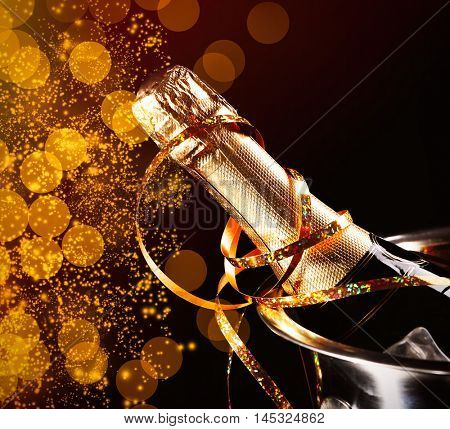 Bottle of champagne with streamer in bucket on black background. Christmas celebration concept.