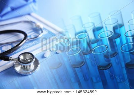 Test-tubes and medical equipment on a light blue background