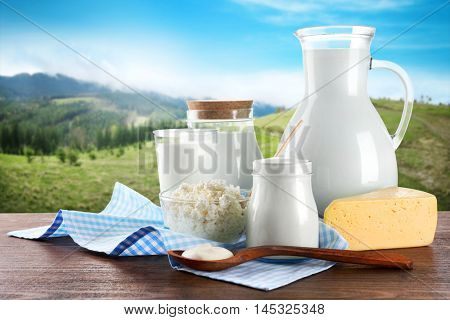 Dairy products on wooden table on mountain slopes