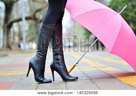 Girl and pink umbrella on a wet sidewalk in the city