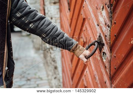 Man hand holding old door knob in medieval town