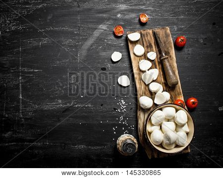 Mozzarella cheese with an old knife and tomatoes. On a black wooden background.