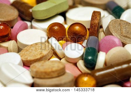 Assorted colorful pills and capsules on white background close up horizontal selective focus medical concept