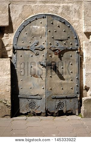 Ancient stone wall with metal forged door background