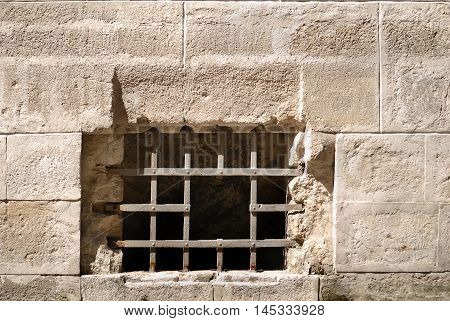 Window lattice from old rusty iron on a stone wall of ancient dungeon