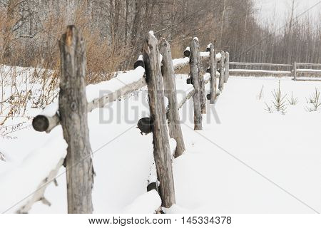 old rough rustic fence, made of logs, covered with snow