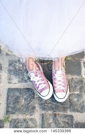 Young adult girl in purple keds and fluffy skirt. Teenager fashion.