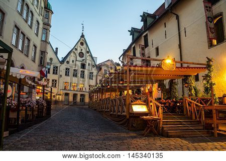 TALLINN, ESTONIA - AUGUST 29, 2015: Old buildings, restaurants and cafes in old historical area of the popular European city in Baltic region. Night view, cloudy sky. Lights and illumination