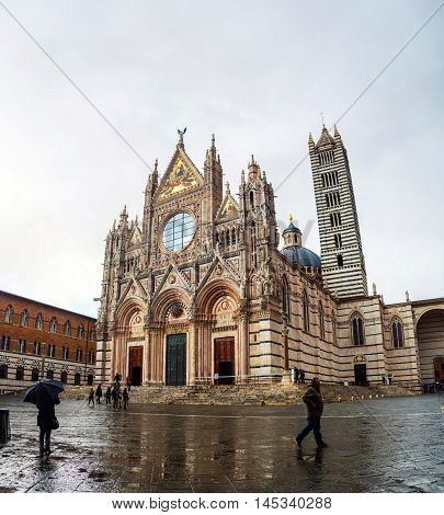 Aerial view of square in front of Cathedral Duomo in Siena, Italy. Cloudy sky and rain, people with umbrellas