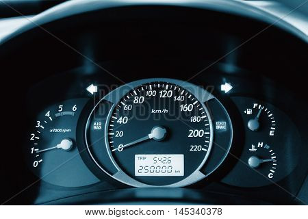 Car Dashboard. Close up image of illuminated car dashboard. 250 000 km without incident, blue colored
