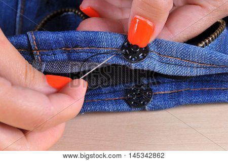 sews a buttons to the cloth (denim). hand with a needle close-up