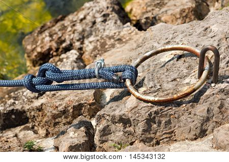 Detail of a rusty mooring ring with a blue nylon rope on the cliff. Garda Lake Verona Italy