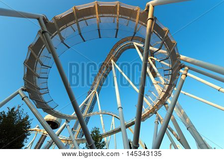 Bottom view of a white roller coaster on a clear blue sky at sunset