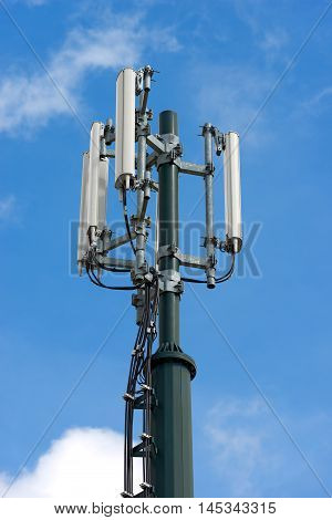 Detail of a telecommunications tower (cell phone) with blue sky and clouds